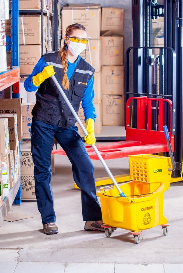 Woman with a mop and bucket wearing a mask - maintenance - San Francisco Audiology