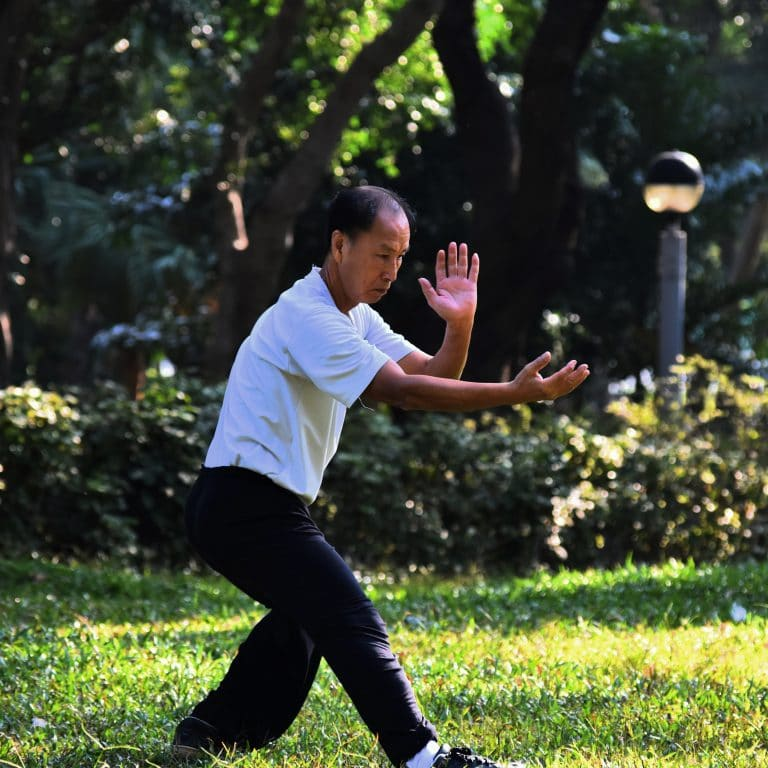 older man doing tai chi in a grassy area