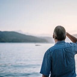 Man looks out at a lake