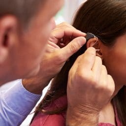 Woman gets a hearing aid fitting