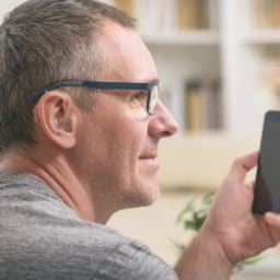 Man with a hearing aid uses smartphone.