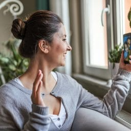 Woman with a hearing aid talks on the phone.