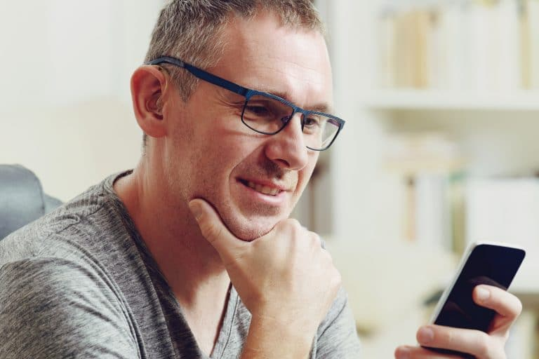 Hearing impaired man with hearing aid using smart phone at home or at office
